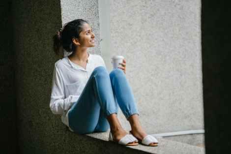 woman posing wearing white dress shirt sitting on window
